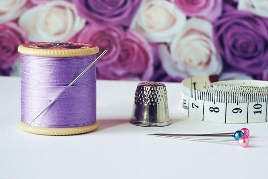 Syning - Frederikssund. Billede af sytråd, nåle, målebånd og et fingerbøl